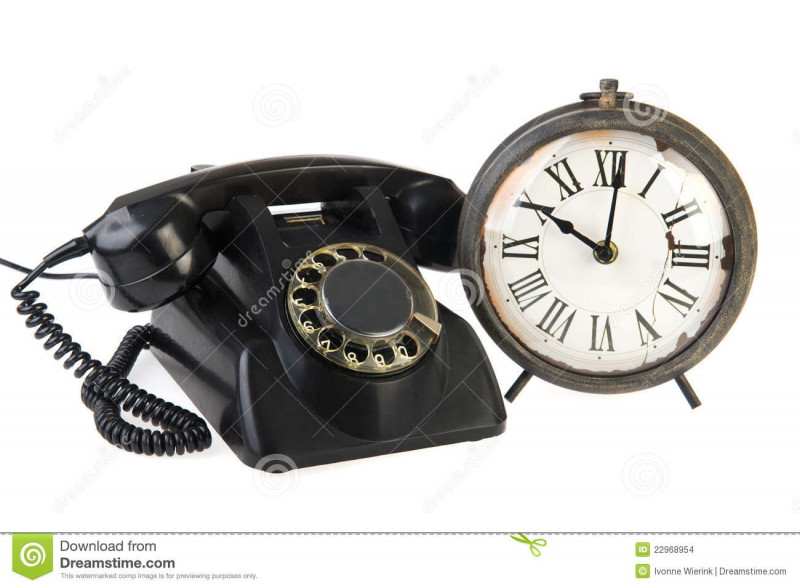 Vintage black telephone and old analoque clock.